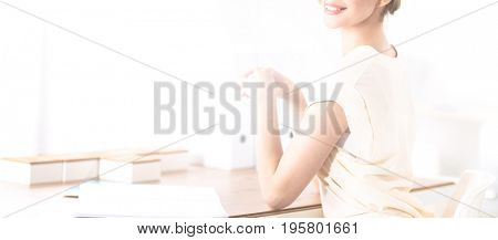 Attractive young businesswoman standing near desk in the office