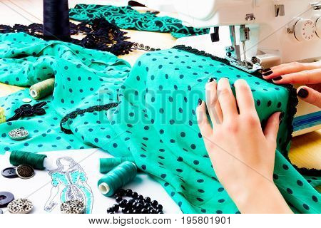Close up of girls hands sewing dress with the help of sewing machine