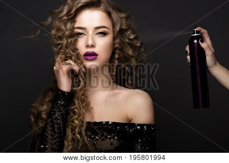 Beautiful brunette model with classic makeup and bottle of hair products. beauty face. Portrait shot in the studio