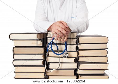 Senior doctor in white tunic and stethoscope leaning on many stacked books and textbooks.