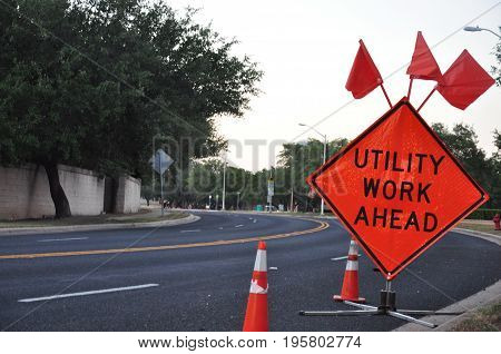 A utility work sign on the road with trees in the background