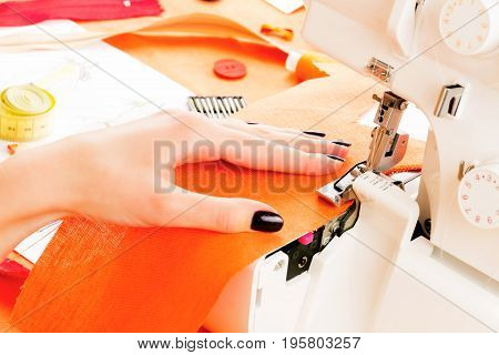 Close up of girls hands sewing dress with the help of sewing machine. Dressmaker's workplace: sewing machine zipper measuring tape sketches