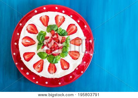 Caramel cheesecake with strawberry on the wooden background top view