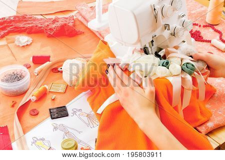 Close up of girls hands sewing dress with the help of sewing machine. Dressmaker's workplace: sewing machine zipper measuring tape sketches spools beads needles pins and other tools.