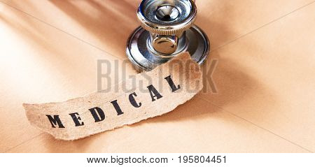 Word medical written on a ripped piece of paper and astethoscope