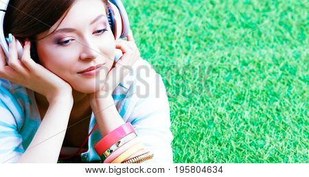 Woman listening to the music sitting on grass