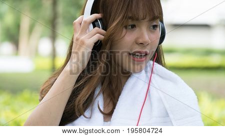 Asian Woman With Headphones. Young Female Girl Listening To Music In Public Park