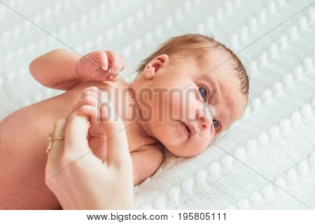 Portrait of newborn baby girl princess with crown on soft white blanket. Mother's hand holding baby.