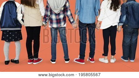 Group of diverse kids students standing in a row holdings hands