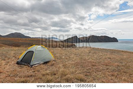 Tourist tent on a promontory near the sea of the day. The concept of traveling with tents