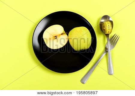 Apple Halves Placed On Black Plate Near Fork And Spoon