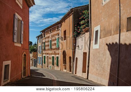 View of traditional colorful houses in ocher and street in the city center of the village of Roussillon. Located in the Vaucluse department, Provence region, southeastern France