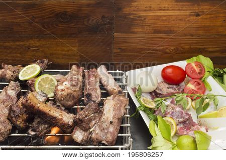 Roasted pork ribs on the barbecue and fresh ribs on the table