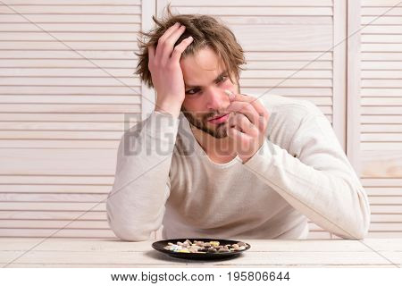 Pills On Plate And Bearded Man. Man With Baffled Face