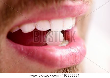 Guys mouth with round pink drug close up. Medical treatment or health concept. Patients teeth hold pill in his teeth isolated on white background selective focus