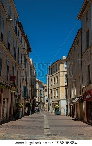 Nimes, France - July 04, 2016. Street view with buildings, shops and sunny blue sky in city center of the ancient town of Nimes. Located in the Gard department, Occitanie region, southern France