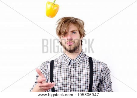 Man With Serious Face Throws Yellow Bell Pepper Up