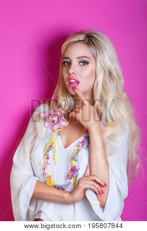 Beauty sexy woman in hawaii costume . Blonde woman with pink lips on pink background .