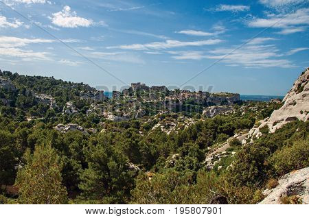 Panoramic View of the village and ruins of the Baux-de-Provence Castle on top of cliff and sunny blue sky. Bouches-du-Rhône department, Provence-Alpes-Côte d'Azur region, southeastern France