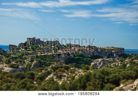 Panoramic View of village and ruins of the Baux-de-Provence Castle on top of cliff and blue sky. Bouches-du-Rhône department, Provence-Alpes-Côte d'Azur region, southeastern France. Retouched photo