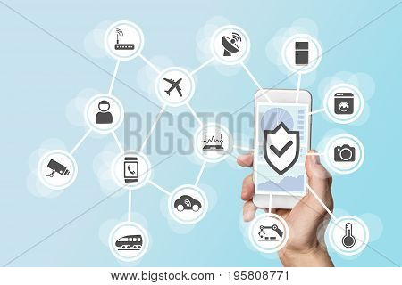 Internet of things security concept with hand holding modern smart phone to control intruders into a network of objects