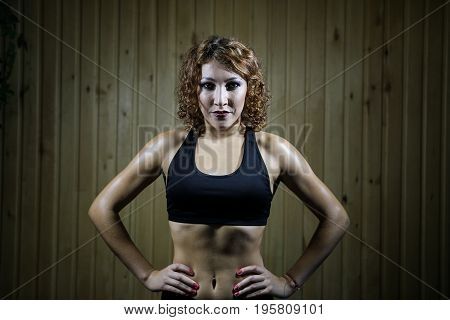 Redhead athletic girl standing in the black sports bra on wooden wall background.