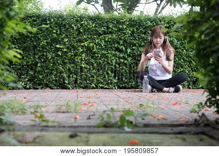 Asian Woman With Headphones. Young Female  Holding Mobile Smart Phone. A Girl Listening To Music In
