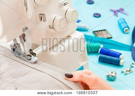 Close up of girls hands sewing dress with the help of sewing machine. Dressmaker's workplace: sewing machine ribbon buttons spools and bows and needles