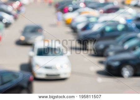 Blur image of parking next to modern shopping mall at peak hour. Cars leave the parking lot, sales retail, season sales
