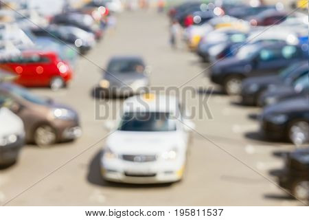 Abstract blurred outdoor car parking area and Cars leave the parking lot, sales retail, season sales, modern shopping mall at peak hour.