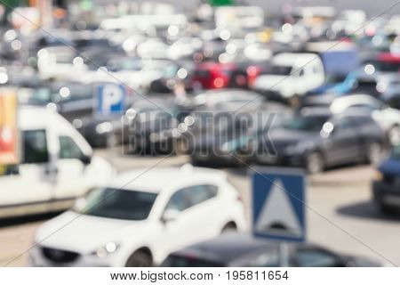 Abstract blurred outdoor car parking lot. Sales retail, season sales, modern shopping mall, peak hour, bokeh background