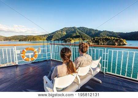New Zealand cruise travel passengers enjoying nature view of ferry boat cruising in Marlborough sounds trip from Picton to Wellington, Cook strait. Couple tourists sitting outside on deck.