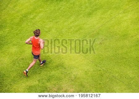 Runner man running on summer grass park jogging healthy lifestyle. People working out cardio top view. Copy space on green texture background.