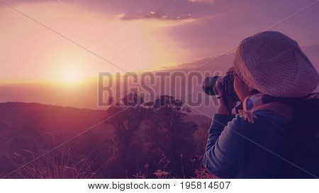 Female backpacker taking photograph at sunset in morning. Travel to Doi Inthanon Chiangmai Thailand.