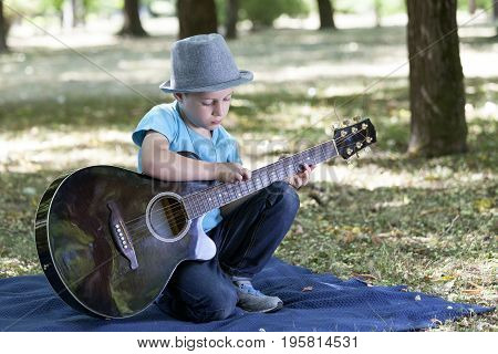Portrait Of A Little Sweet Boy Sitting In A Park And Playing A Guitar