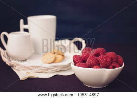 A Bowl With Raspberries. Cup Of Coffee, Cookies A Jug Of Milk On A Straw Tray. Black Background. Vin