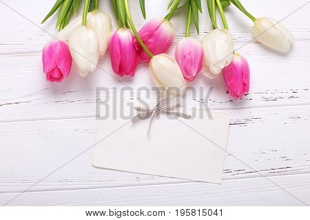 Empty tag and pink and white tulips flowers on white wooden background. Selective focus. Place for text.