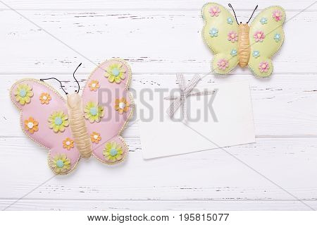 Two decorative butterflies and empty tag on vintage wooden background. Top view. Flat lay. Place for text.