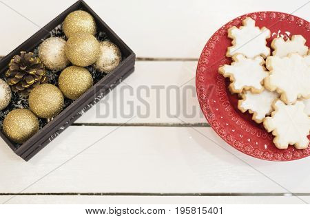 Golden Christmas Balls In A Wooden Crate, Christmas Cookies Shaped In Snowflakes In Red Tray On A Wh