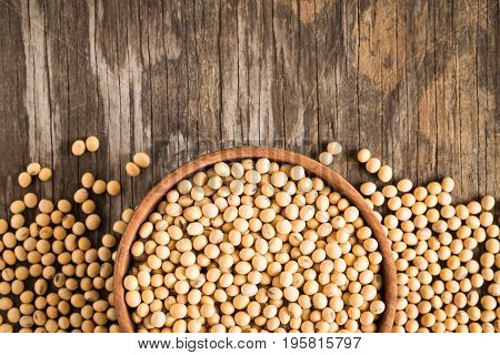 Soybeans on old wood background, top view