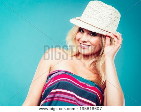 Summer trendy fashionable outfit ideas concept. Blonde woman wearing colorful striped strapless shirt and white fedora hat