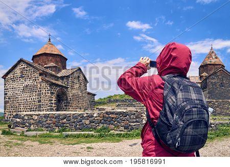 Female tourist taking photo of ancient monastery in Armenia using smartphone