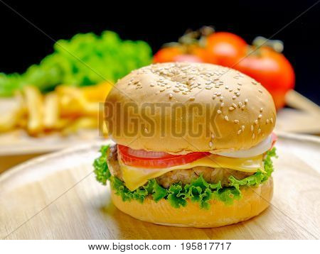 Burger on wooden plate with french fries and vegetables