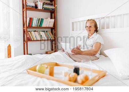 Elderly Woman Having Breakfast In Bed Whilst Using Her Tablet
