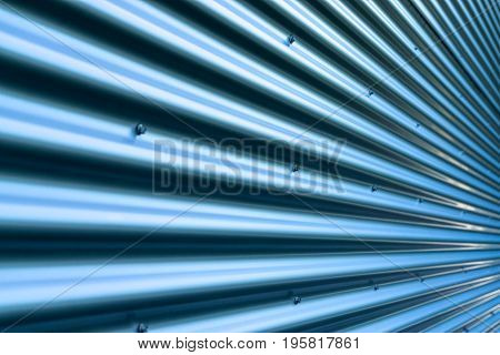 Closeup stainless steel corrugated sheet. Ridged reinforced metal surface for protection. Blue metallic background texture with shiny reflection.