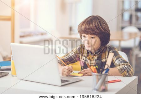 Sticky notes. Smart cute good looking boy holding a pencil and writing on sticky notes while sitting in front of the laptop