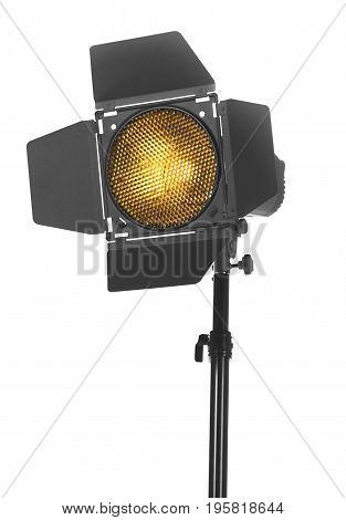 Close-up of black studio lighting on a tripod stand, isolated on the white background. Photo-studio with lighting equipment. The photo of the honeycomb is glowing.
