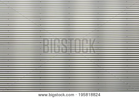 Closeup stainless steel corrugated sheet. Ridged reinforced metal surface for protection. Metallic background texture with shiny reflection.