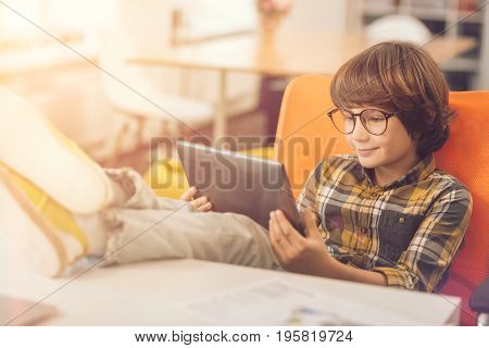 Watching a film. Happy delighted cute kid sitting in the chair and holding a tablet while watching a film