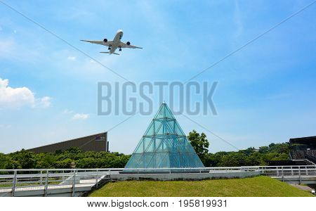 TAIPEI, TAIWAN - JULY 1, 2017 - Commercial passenger plane deploying landing gear over Taipei Expo Park to land at Songshan Airport
